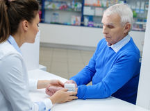 Beautiful young woman pharmacist measuring blood pressure to senior man customer in pharmacy. Beautiful young women pharmacist measuring blood pressure to royalty free stock photography