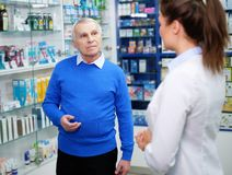 Beautiful young woman pharmacist showing drugs to senior man customer in pharmacy. Beautiful young women pharmacist showing drugs to senior men customer in royalty free stock image