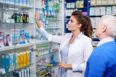 Beautiful young woman pharmacist showing drugs to senior man customer in  pharmacy. Stock Photo