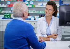 Beautiful young woman pharmacist showing drugs to senior man customer in pharmacy. Beautiful young women pharmacist talking with senior men customer in pharmacy stock images