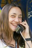 Beautiful young woman in a phone booth. The girl is talking on the phone from the payphone. woman talking by public telephone royalty free stock image