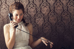 Beautiful young woman on the phone in living room Stock Image