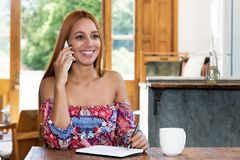 Beautiful young woman at phone talking with other women. Beautiful young woman at phone talking with other woman at rural home Stock Photo