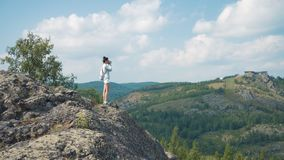 Woman photographer takes a picture of a mountain landscape on the camera stock video footage