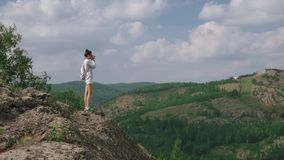 Woman photographer takes a picture of a mountain landscape on the camera stock footage