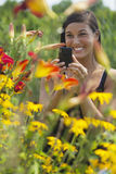 Beautiful Young Woman Photographing Flowers Stock Images