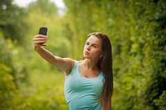 Beautiful young woman photographing herself Royalty Free Stock Photo