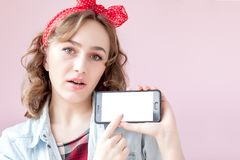 Beautiful young woman with pin-up make-up and hairstyle over pink background with mobile phone with copy space.  royalty free stock image