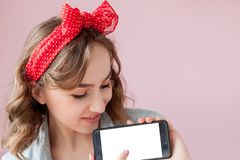 Beautiful young woman with pin-up make-up and hairstyle over pink background with mobile phone with copy space.  royalty free stock images