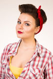 Beautiful young woman with pin-up make-up and hairstyle posing over pink background Royalty Free Stock Images