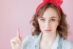 Beautiful young woman with pin-up make-up and hairstyle. Studio shot on pink background.  royalty free stock photo