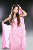 Beautiful young woman in pink chiffon dress. Makeup. Long wavy h Stock Photos