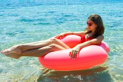 Beautiful young woman with pink circle relaxing in blue sea royalty free stock photography