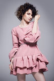 Beautiful young woman in a pink dress with frills. Stands on a bright gray background Stock Image