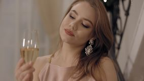 Beautiful young woman in pink dress looking at wineglass and smiling stock video
