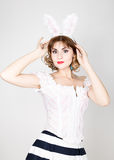 Beautiful young woman in pink dress and rabbit ears, standing, posing. Stock Photography