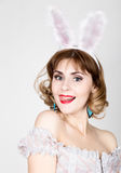 Beautiful young woman in pink dress and rabbit ears, standing, posing. Royalty Free Stock Images