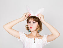 Beautiful young woman in pink dress and rabbit ears, standing, posing. Royalty Free Stock Photo