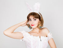 Beautiful young woman in pink dress and rabbit ears, standing, posing. Stock Image