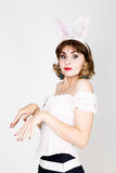 Beautiful young woman in pink dress and rabbit ears, standing, posing. Stock Images