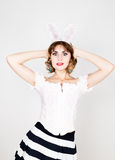 Beautiful young woman in pink dress and rabbit ears, standing, posing. Stock Photos