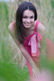 Beautiful young woman in pink dress among reed Stock Image