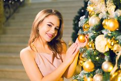 Beautiful young woman in a pink elegant evening dress staying in a chic hall near christmas tree with yellow ball in her hands on stock image