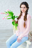 Beautiful young woman with pink flowers bouquet Stock Images