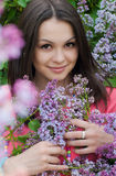Beautiful young woman among pink lilac Royalty Free Stock Photography