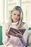 Beautiful Young Woman in Pink Sweater Reading a Book Stock Photo