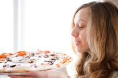 Beautiful young woman with pizza in hands Royalty Free Stock Images