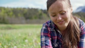 Beautiful young woman in plaid shirt weaves a wreath of meadow dandelion flowers. Portrait of smiling girl. 4k stock video