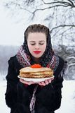 Woman with a plate of pancakes and red caviar royalty free stock image