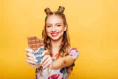 Woman with playful look bites huge chocolate. Beautiful young woman with playful look bites huge chocolate. Stylish girl with blonde curly hair. Stylish girl in Royalty Free Stock Image