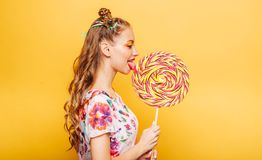 Woman with playful look eating candy Stock Images