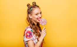 Woman with playful look lick candy with tongue. Beautiful young woman with playful look lick candy with tongue. Stylish girl with blonde curly hair. Portrait of Stock Image