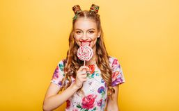 Woman with playful look lick candy with tongue. Beautiful young woman with playful look lick candy with tongue. Stylish girl with blonde curly hair. Portrait of Royalty Free Stock Image