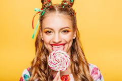 Woman with playful look lick candy with tongue. Beautiful young woman with playful look lick candy with tongue. Stylish girl with blonde curly hair. Portrait of Royalty Free Stock Photography