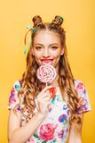 Woman with playful look lick candy with tongue. Beautiful young woman with playful look lick candy with tongue. Stylish girl with blonde curly hair. Portrait of Royalty Free Stock Photos