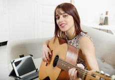 Beautiful young woman playing the acoustic guitar Royalty Free Stock Photos