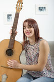 Beautiful young woman playing the acoustic guitar Stock Photography