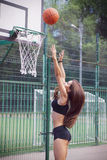 Beautiful young woman playing basketball outdoors Royalty Free Stock Images