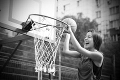Beautiful young woman playing basketball outdoors Royalty Free Stock Photos