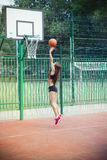 Beautiful young woman playing basketball outdoors Stock Photos