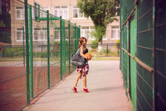 Beautiful young woman playing basketball outdoors Stock Photography