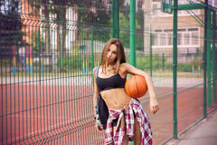 Beautiful young woman playing basketball outdoors Royalty Free Stock Photo