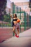 Beautiful young woman playing basketball outdoors Royalty Free Stock Photos