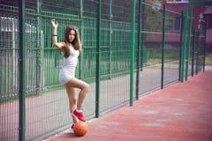 Beautiful young woman playing basketball outdoors Stock Photo