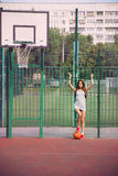 Beautiful young woman playing basketball outdoors Stock Photo