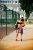 Beautiful young woman playing basketball outdoors Stock Images